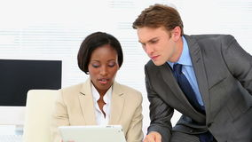Business people talking together at desk with tablet. In the office stock footage