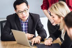 Business people talking together look at computer laptop in meeting royalty free stock photos