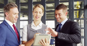 Business people talking together while looking tablet stock footage