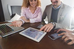 Business People Team Group Discussing Financial Diagram Report On Tablet Screen Businesspeople Meeting Sitting At Desk Stock Photography