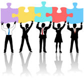 Business people team hold puzzle solution. Team of business people collaborate holding up jigsaw puzzle pieces as a solution to a problem Royalty Free Stock Photo