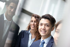 Business people team. Meeting in front of the office window, asian and caucasian Stock Image