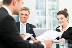 Business people - team meeting in an office. The boss with his employees Stock Photography