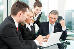 Business people - team meeting in an office. With laptop, the boss with his employees Stock Photo