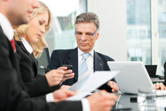 Business people - team meeting in an office. The boss is checking his mails Royalty Free Stock Photo