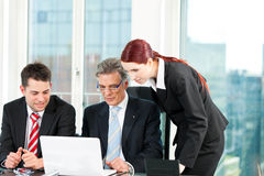 Business people - team meeting in an office. Business - team meeting in an office with laptop, the boss with his employees Royalty Free Stock Photo