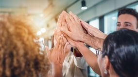 Business people teamimg up and making highfive to cheer up team spirit. To success stock images
