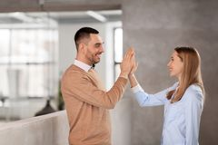 Man and woman making high five at office Stock Photo