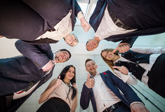 Business, people and teamwork concept - smiling group of businesspeople standing in circle,View from underneath of a group of bus. Inesspeople standing in a royalty free stock photo