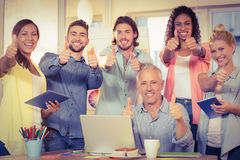 Business people with technologies showing thumbs up Stock Photo