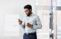 Businessman with smartphone and coffee at office. Business, people and technology concept - african american businessman with smartphone having break and Stock Photo
