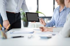 Close up of business team with tablet pc at office stock image