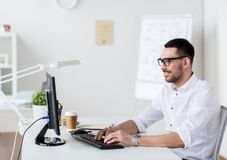 Businessman typing on computer keyboard at office Stock Photos
