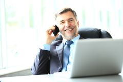 Business, people and technology concept - happy smiling businessman with laptop computer office. Business, people and technology concept - happy smiling mature Stock Photography