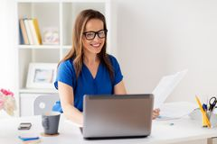 Happy woman with laptop working at home or office. Business, people and technology concept - happy smiling woman with laptop computer working at home or office Stock Image