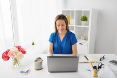 Happy woman with laptop working at home or office. Business, people and technology concept - happy smiling woman with laptop computer working at home or office Stock Photo
