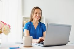 Happy woman with laptop working at home or office. Business, people and technology concept - happy smiling woman with laptop computer working at home or office Royalty Free Stock Photography