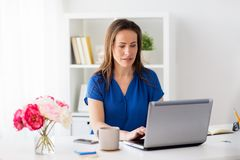 Happy woman with laptop working at home or office. Business, people and technology concept - happy smiling woman with laptop computer working at home or office Royalty Free Stock Images