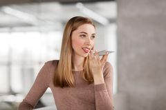 Woman using voice recorder on smartphone at office. Business people, technology and corporate concept - happy smiling businesswoman using voice command recorder Royalty Free Stock Photo