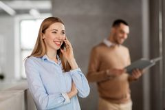 Businesswoman calling on smartphone at office Royalty Free Stock Images