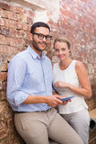 Business people text messaging against brick wall Royalty Free Stock Photos