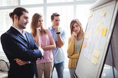 Business people thinking while looking at blueprints stock image