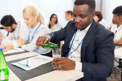 Businessman drinking water at business conference. Business, people and thirst concept - young businessman pouring himself drinking water in a glass at Stock Photos
