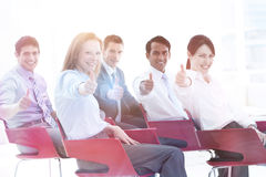 Business people with thumbs up at a conference Stock Photos