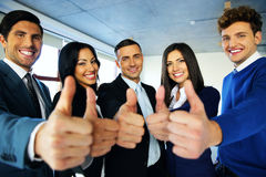 Business people with thumbs up sign. Portrait of happy young business people with thumbs up sign Stock Photography