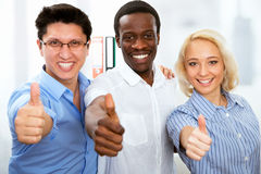 Business people with thumbs up. And smilingin in office Stock Photo