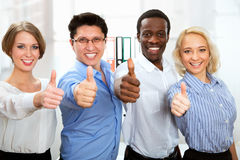 Business people with thumbs up. And smilingin in office Stock Photography