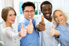 Business people with thumbs up. And smilingin in office Stock Photos