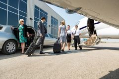 Business People About To Board Private Jet. Airhostess and pilot greeting business people before boarding private jet Royalty Free Stock Photography