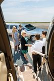 Business People About To Board Private Jet. Airhostess and pilot greeting corporate people before boarding private jet Royalty Free Stock Image
