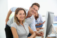 Business people in training. Middle-aged business people working on deskop computer royalty free stock photo