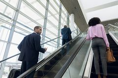 Business People Travelling Up An Escalator Royalty Free Stock Photos