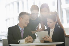 Business people using digital tablet together in office cafeteria Stock Photo