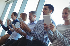 Business people using digital tablets at office. Low angle view of business people using digital tablets by window at office Royalty Free Stock Photo