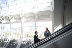 Business people using escalator in airport Stock Image