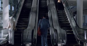 Business people using escalator in a modern office 4k. Overview of diverse Business people using escalator in a modern office. Businessman using mobile phone 4k stock video