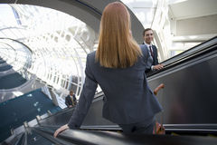 Business people using escalators in airport Royalty Free Stock Photography
