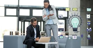 Business people using laptop by bulb sign in office Stock Photography