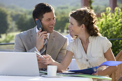 Business people using laptop and cell phone at caf? Stock Photos