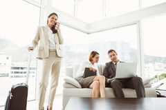 Business people using laptop and colleague with luggage Royalty Free Stock Photo