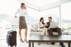 Business people using laptop and colleague with luggage Royalty Free Stock Image