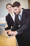 Business people using laptop by counter. Happy business people using laptop by counter at office Stock Photos