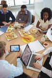Business people using laptop and digital tablets around breakfast table Stock Photography