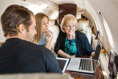 Business People Using Laptop In Private Jet Stock Image