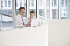 Business people using laptop on railing in office Stock Photography