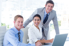 Business people using laptop. Three young business people using laptop in office Stock Images